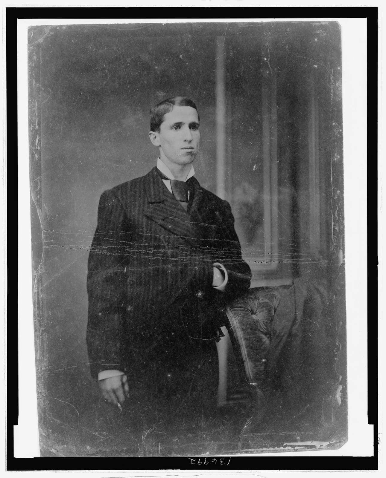 [Full-length portrait of a young man, standing with one hand in suit jacket]