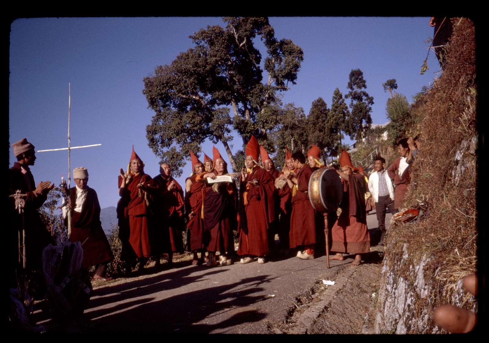 [Lamas praying as they walk down the mountain to perform religious sacrifice, Sikkim]