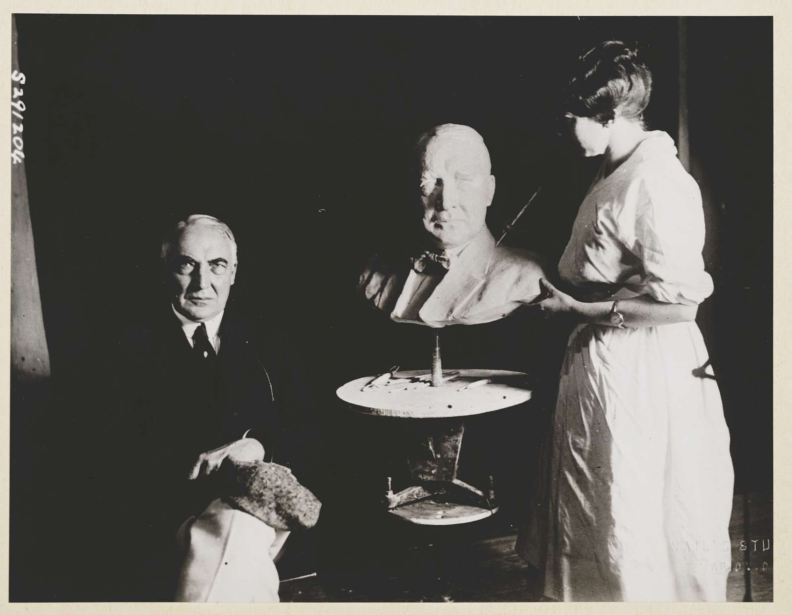 [Sculptress, Helen Osborn, making a head-and-shoulders sculpture of Warren Harding, with Harding posing beside the sculpture]