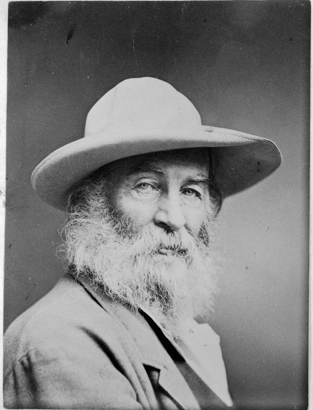 [Walt Whitman, head-and-shoulders portrait, facing front, wearing hat]