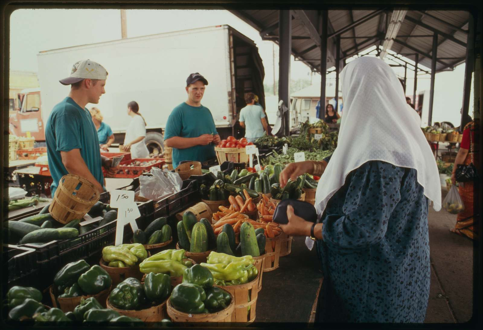 Woman (probably Arabic) wearing head scarf buys produce from a stand.