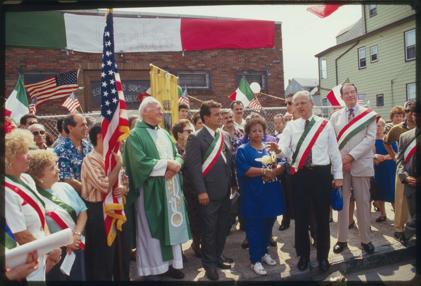 At the conclusion of the procession, dignitaries stand in front of the Montescaglioso Club, on Lewis Street; the tall man to the right is Congressman Herbert Klein, and the man to his right is Paterson mayor William Pascrell.