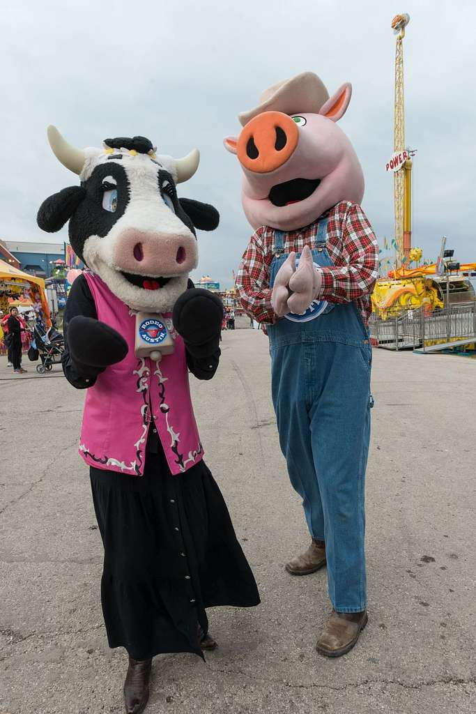 Costumed cow and pig walk the carnival grounds at Rodeo Austin, the city's annual stock show and rodeo. Austin, Texas