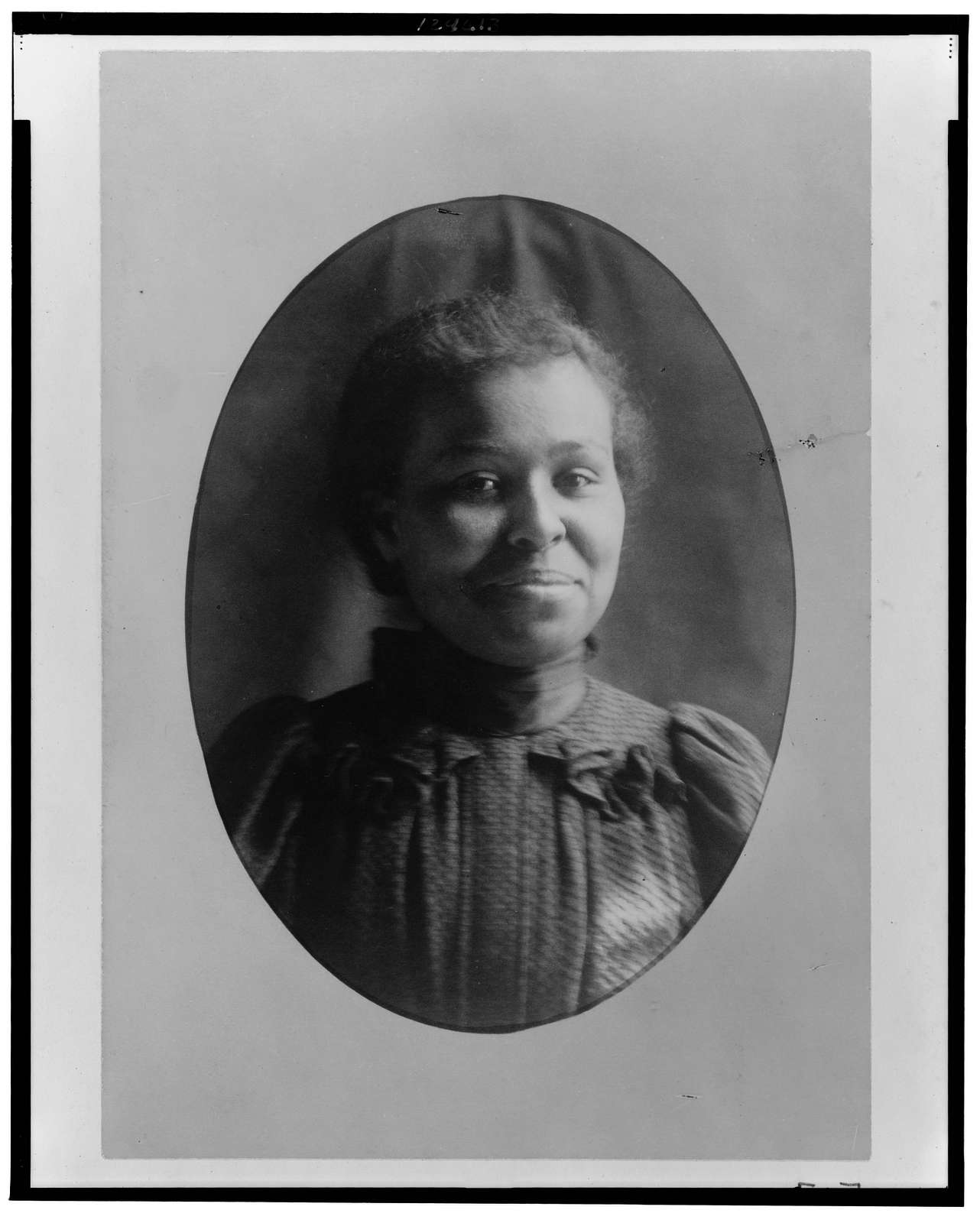 [African American girl, head-and-shoulders portrait, facing front, smiling]