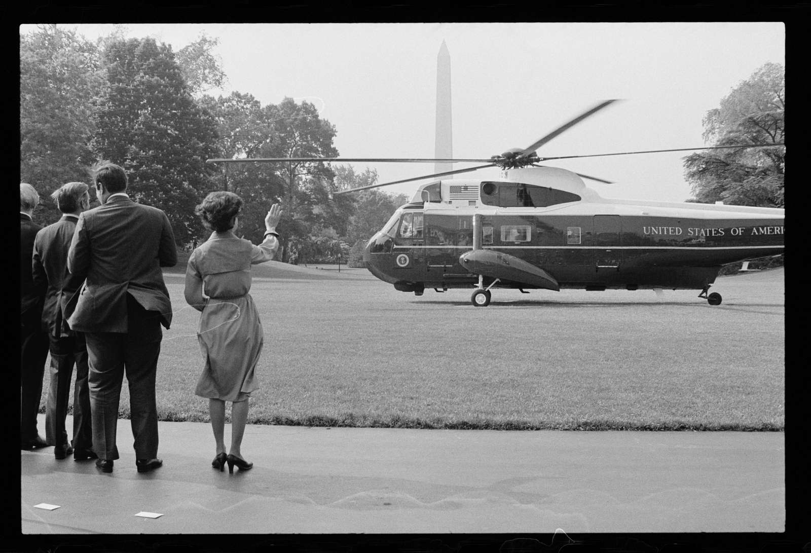 [Helicopter blades begin turning as First Lady Rosalynn Carter and unidentified men wave goodbye to President Jimmy Carter as he departs from the White House lawn, Washington, D.C.]