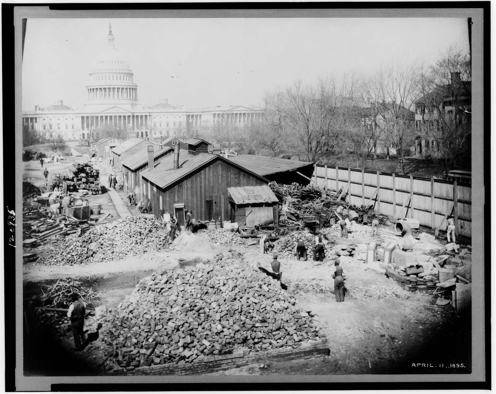 [Sheds, piles of bricks and workers during construction of the Library of Congress Thomas Jefferson Building, Washington, D.C., with the U.S. Capitol in the background]