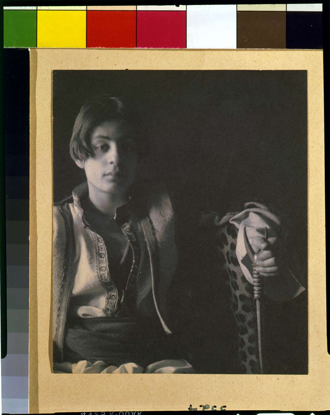 [Kahlil Gibran in Middle Eastern(?) costume with leopard skin and staff, seated]