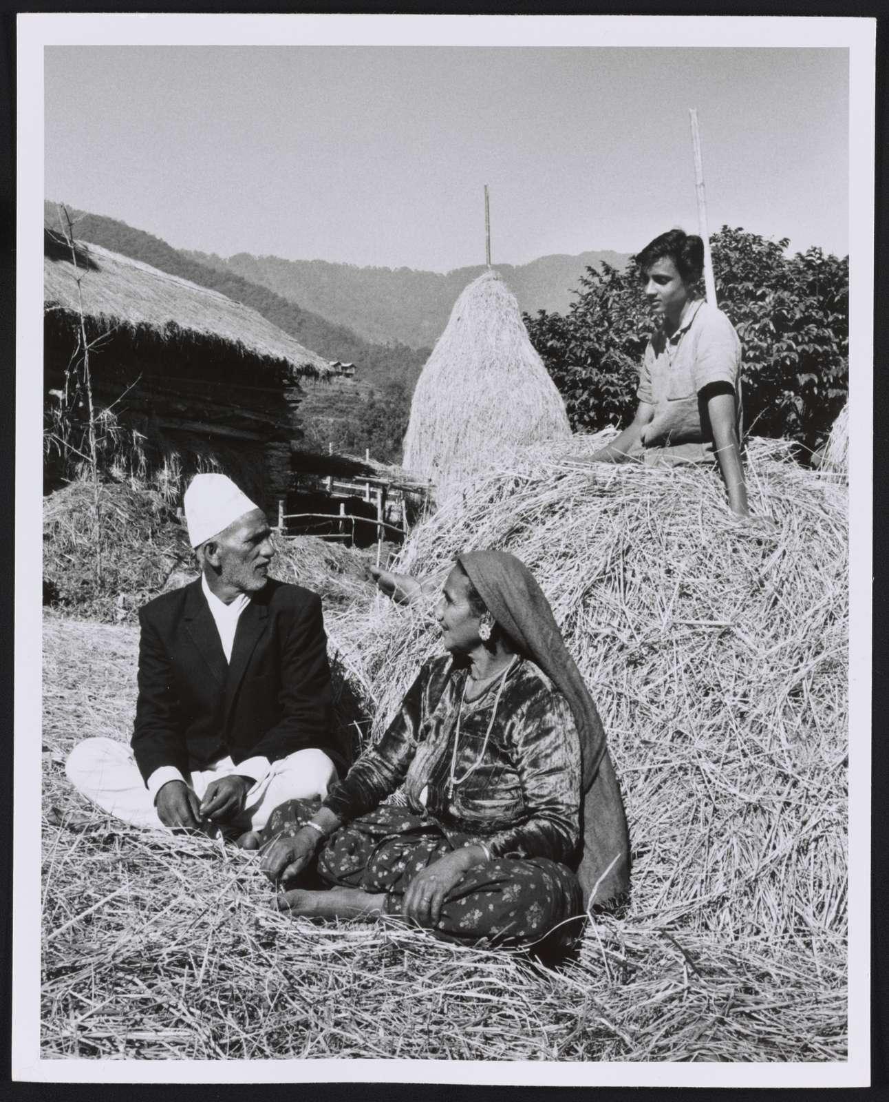 [Nepalese family sitting outside on haystacks, Sikkim]