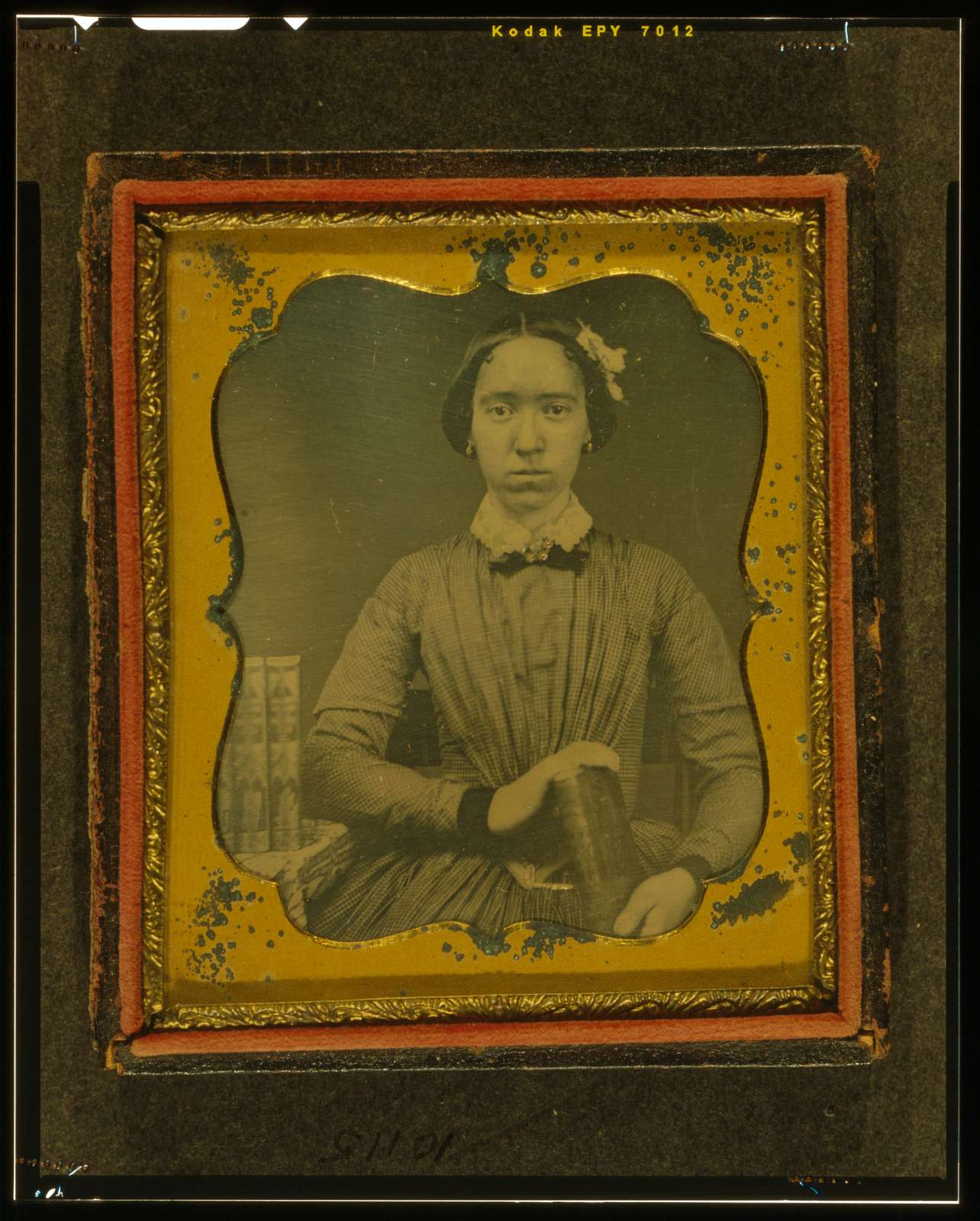 [Unidentified woman holding book, with books on table to her right]