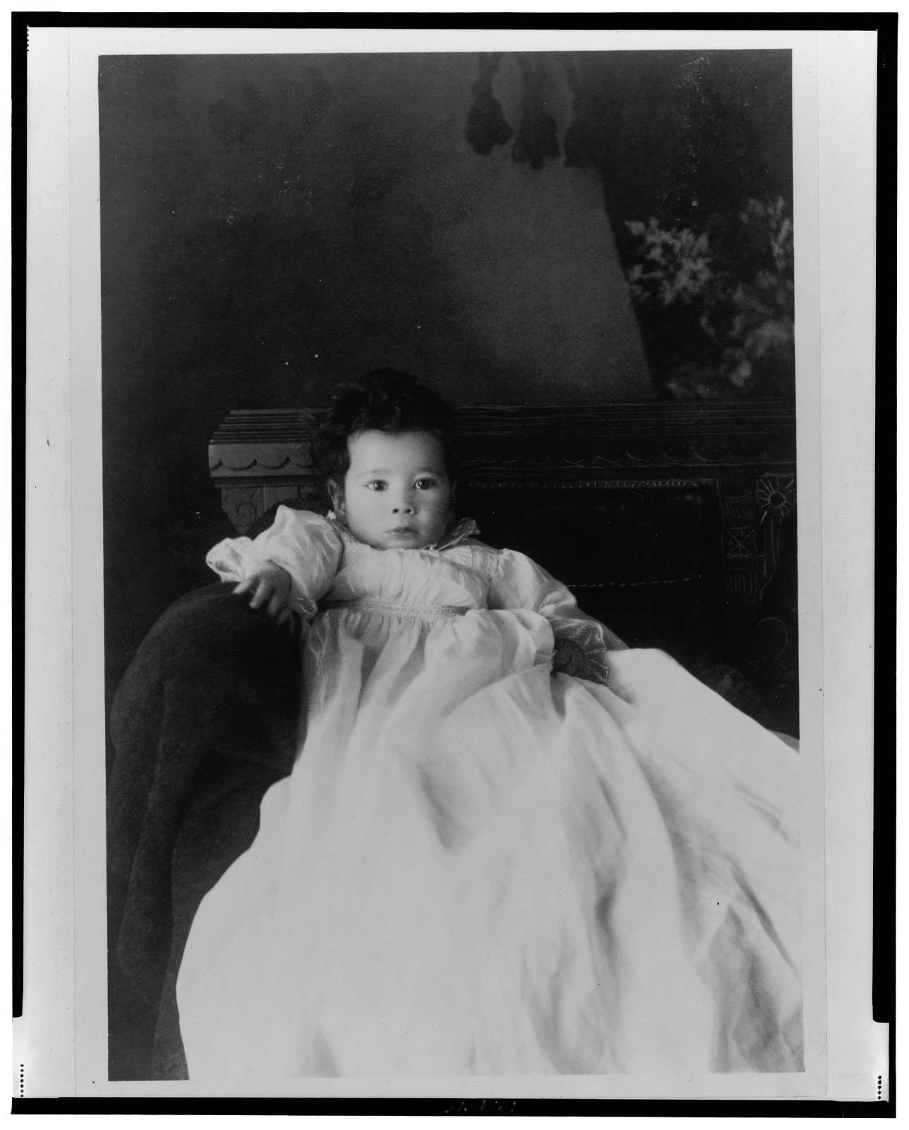 [African American infant, seated in chair, wearing christening gown, facing front]
