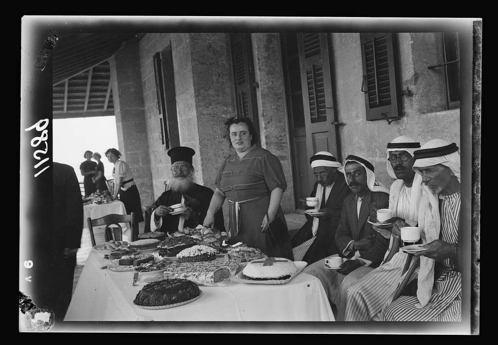 Galilee trip. Nazareth, afternoon fete in aid of the Red Cross & Knights of St. John. Nazareth ladies & ladies of government officials serving tea to Arab guest & Greek Orthodox Prelate