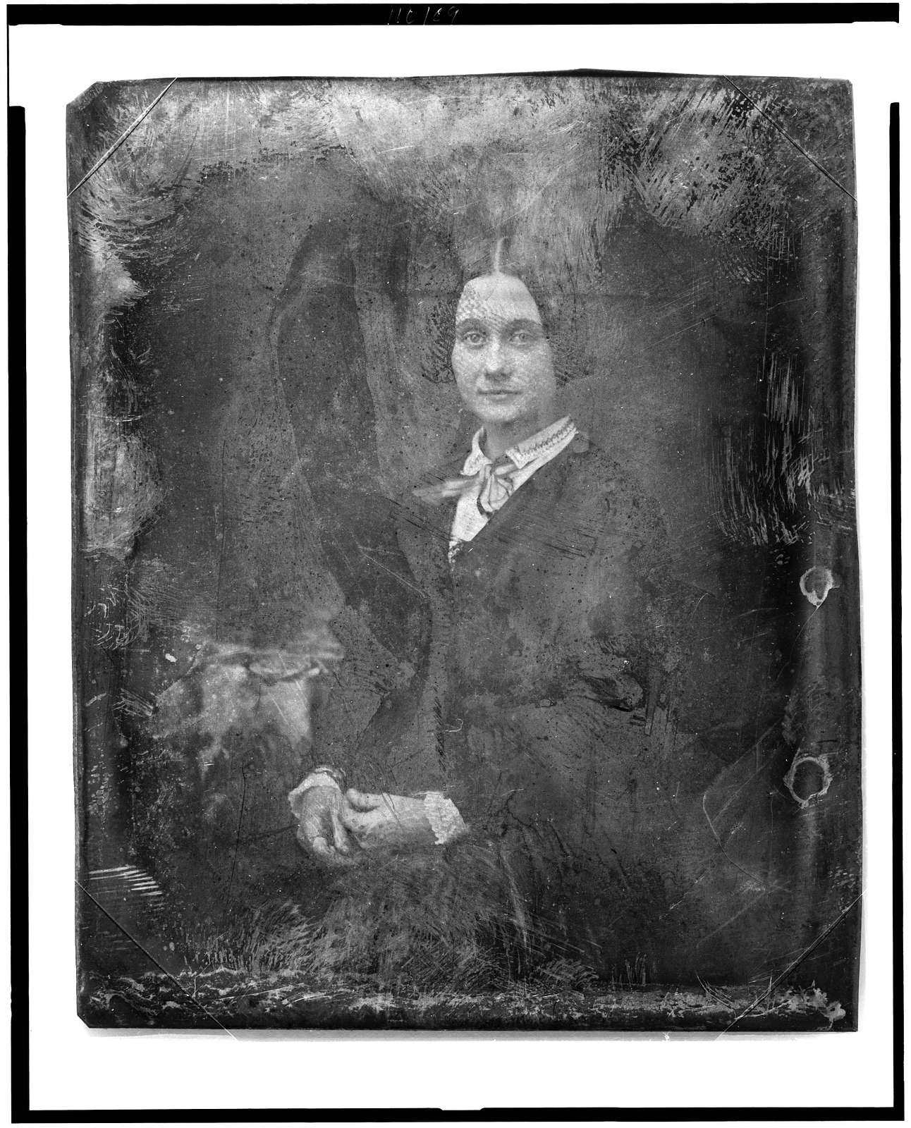 [Unidentified woman, three-quarter length portrait, facing front, seated beside small table with tablecloth]