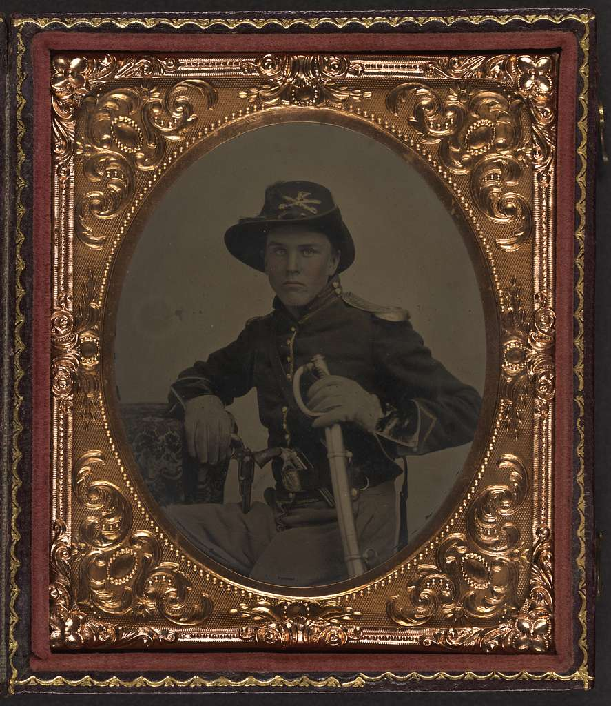 [Unidentified soldier in Union uniform with gauntlets, shoulder scales, and cavalry Company K Hardee hat holding dual Colt Model 1855 Root sidehammer pistols and cavalry saber]