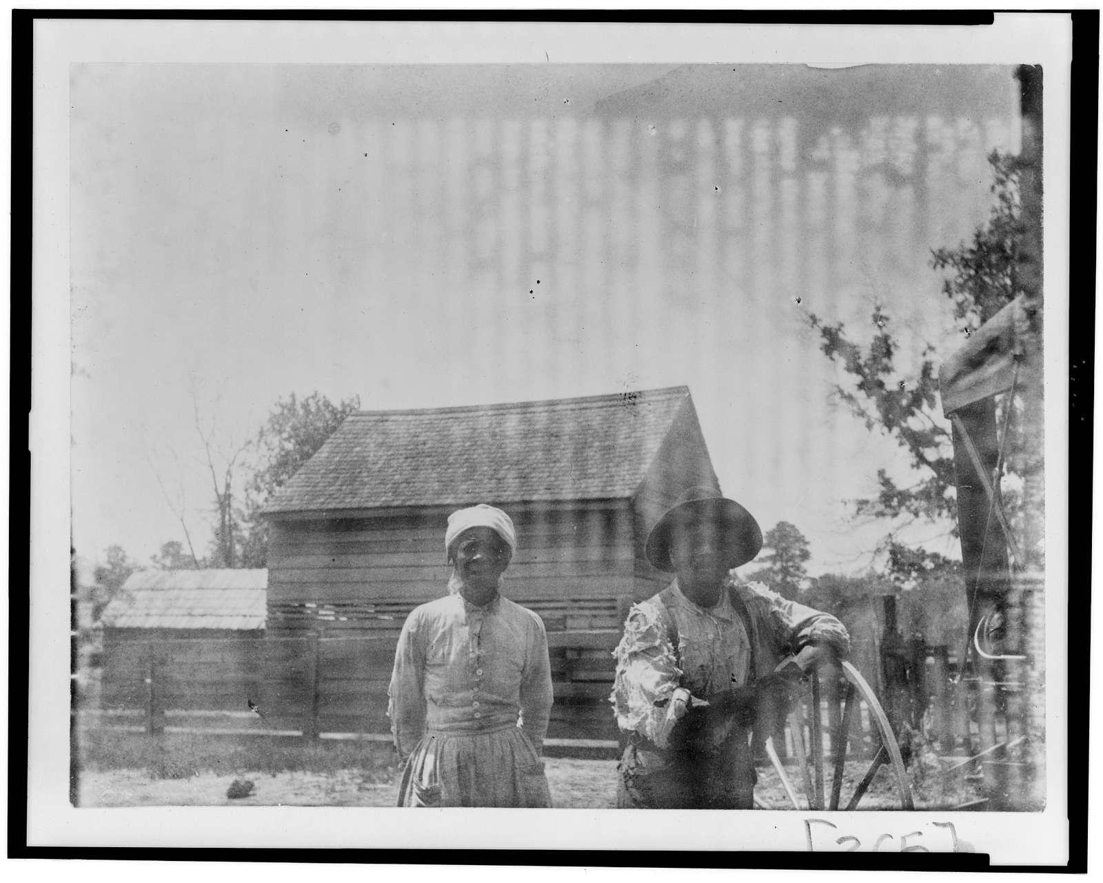 [African American man and woman, half-length portrait, standing in barnyard(?)]