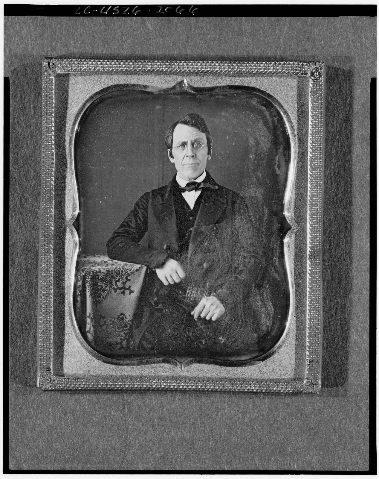 [Unidentified man wearing spectacles, half-length portrait, seated, facing front, arm on table with tablecloth]