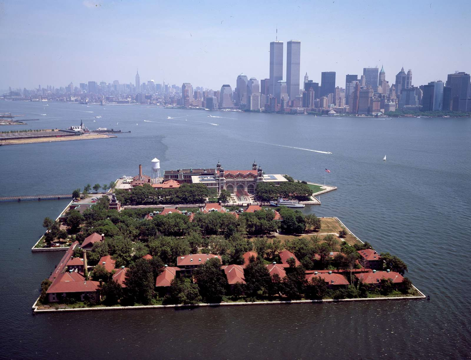 Aerial view of the Ellis Island immigration station, with the World Trade Center Twin Towers, New York City, in the distance