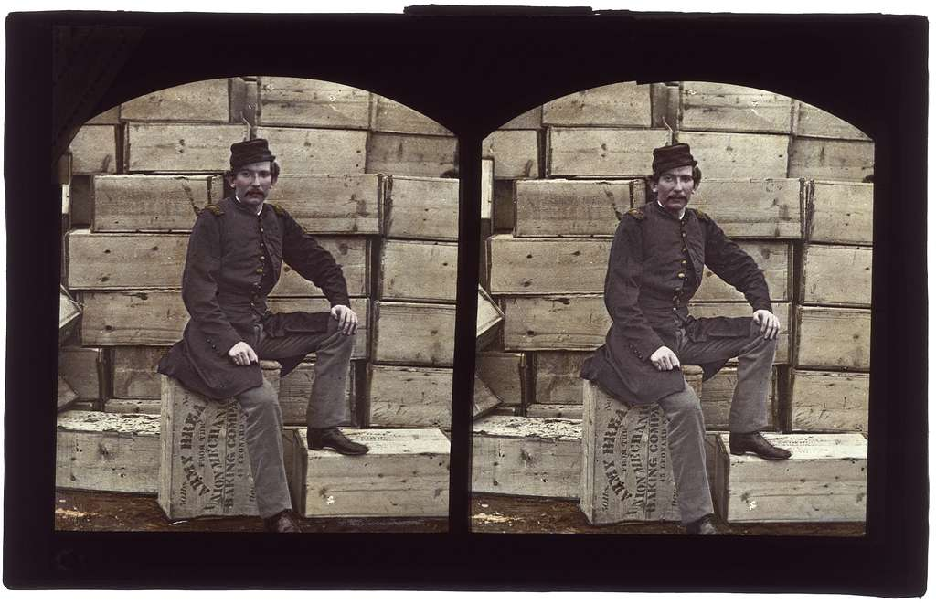 [Captain James William Forsyth, Provost Marshall of 18th Regular Army Infantry Regiment, sitting atop a crate of hardtack at Aquia Creek Landing, Virginia]