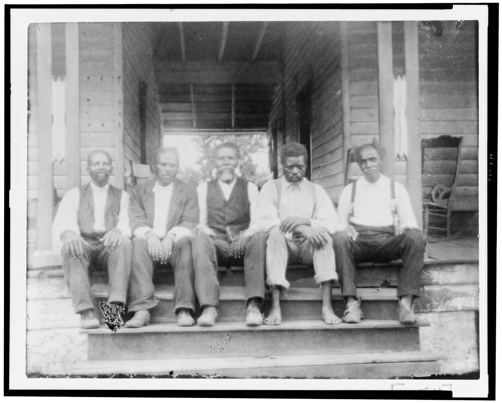 [African American men seated on porch steps]