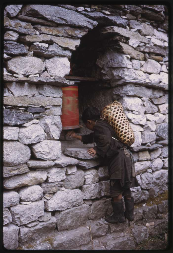 [Boy with basket on back, reaching into a stone structure to turn a prayer wheel, Lachung, Sikkim]