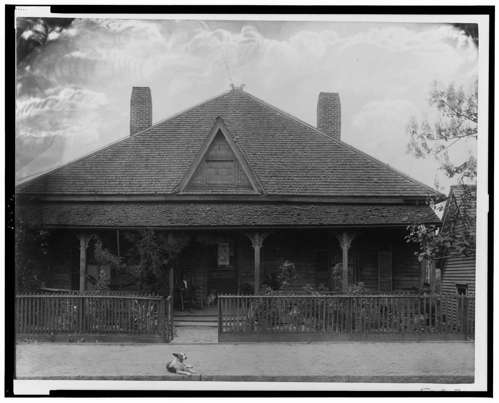 [Exterior view of house with picket fence, man and dog seated on porch and a dog lying on the sidewalk]