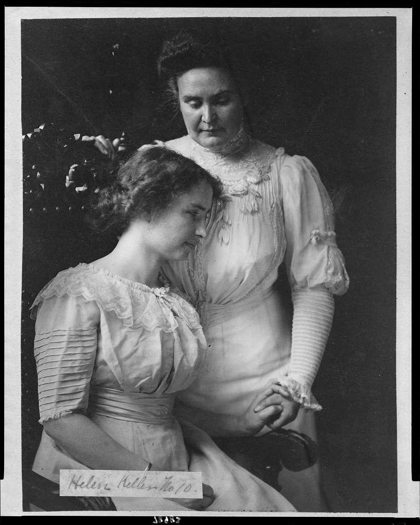[Helen Keller, three-quarter length, seated, facing right; holding hand of her teacher, Mrs. John A. Macy (Anne Mansfield Sullivan)]