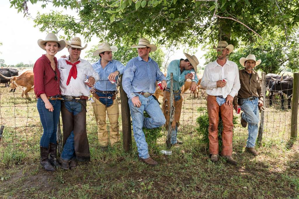 Cowhands, including cowgirl Lacey Elick Hollis, left, take a break from branding longhorns at the 1,800-acre Lonesome Pine Ranch, a working cattle ranch that is part of the Texas Ranch Life ranch resort near Chappell Hill in Austin County, Texas