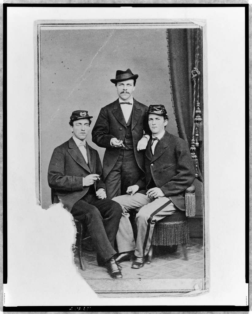 [Unidentified group of three men, full-length portrait, two seated, one standing in the background, facing front]