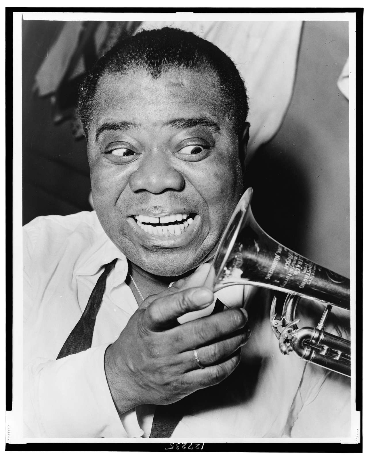 [Louis Armstrong, head-and-shoulders portrait, facing front, looking at trumpet] / World Telegram & Sun photo by Herman Hiller.
