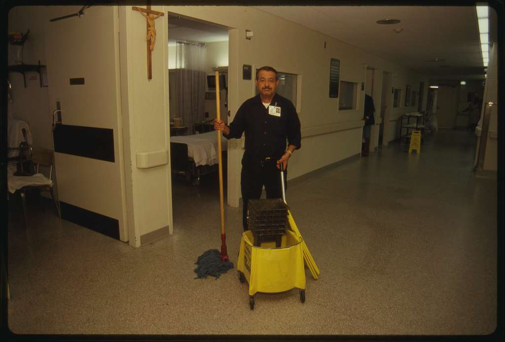 Maintenance worker Jesus Ochora mops a floor.