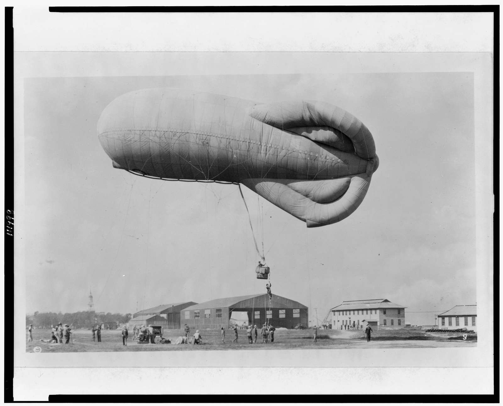 """[""""Pilot"""" climbing up rope to get into basket (gondola) suspended below observation kite balloon during training at the U.S. Naval Air Station, Hampton Roads, Virginia]"""