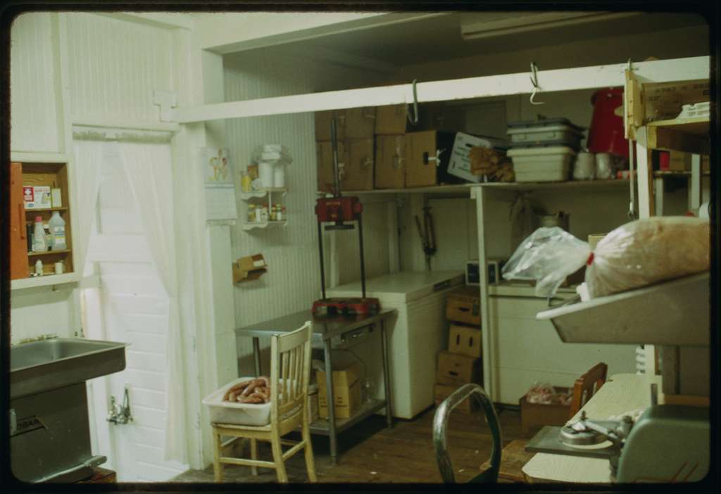 The room in the rear of the shop where sausage is made and other items, such as tripe, are prepared; sausage is visible in a container placed on a chair.