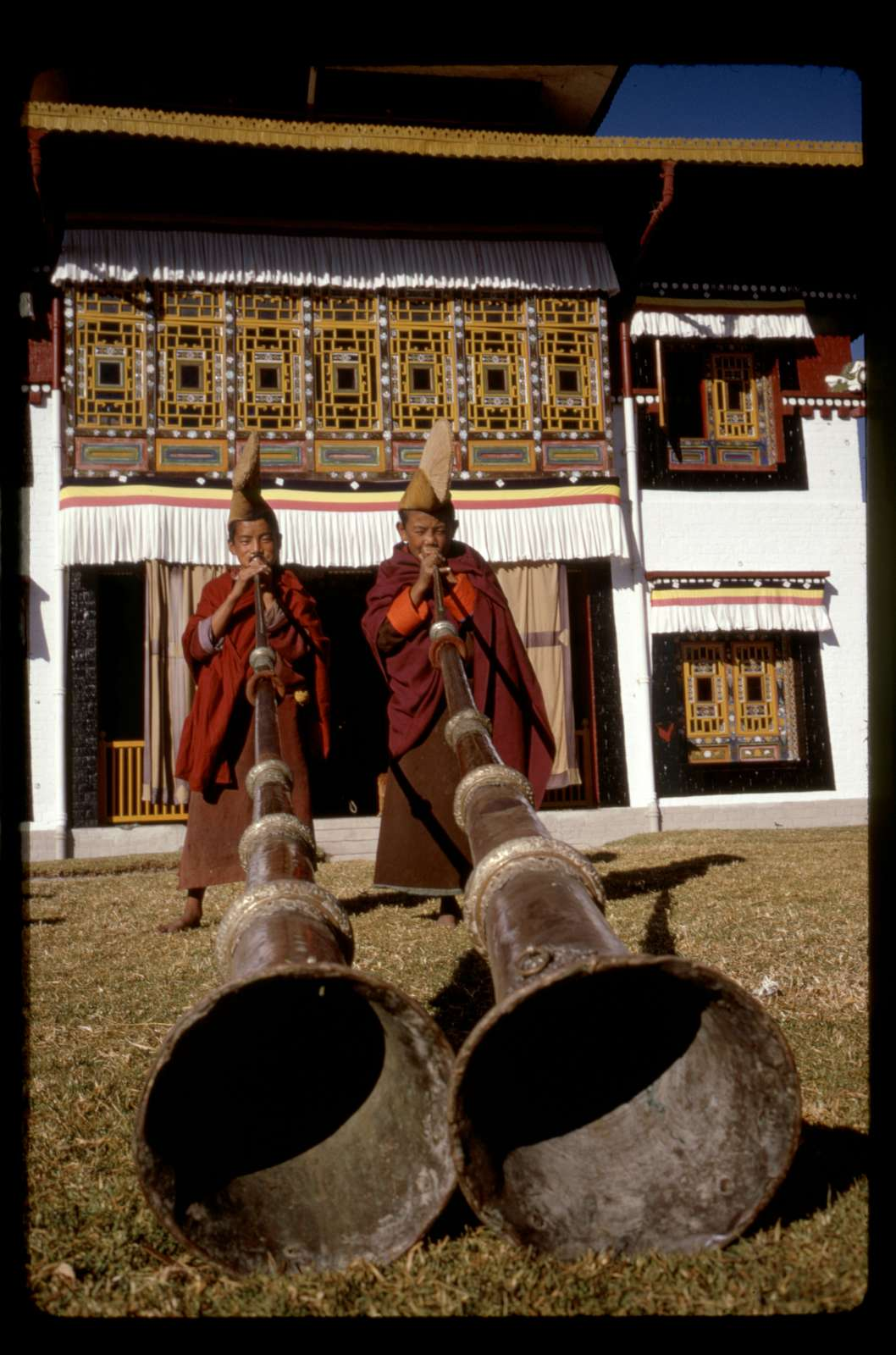 [Boys blowing gyalings in front of the Tsuklakhang Main Temple (Palace Temple), Gangtok, Sikkim]