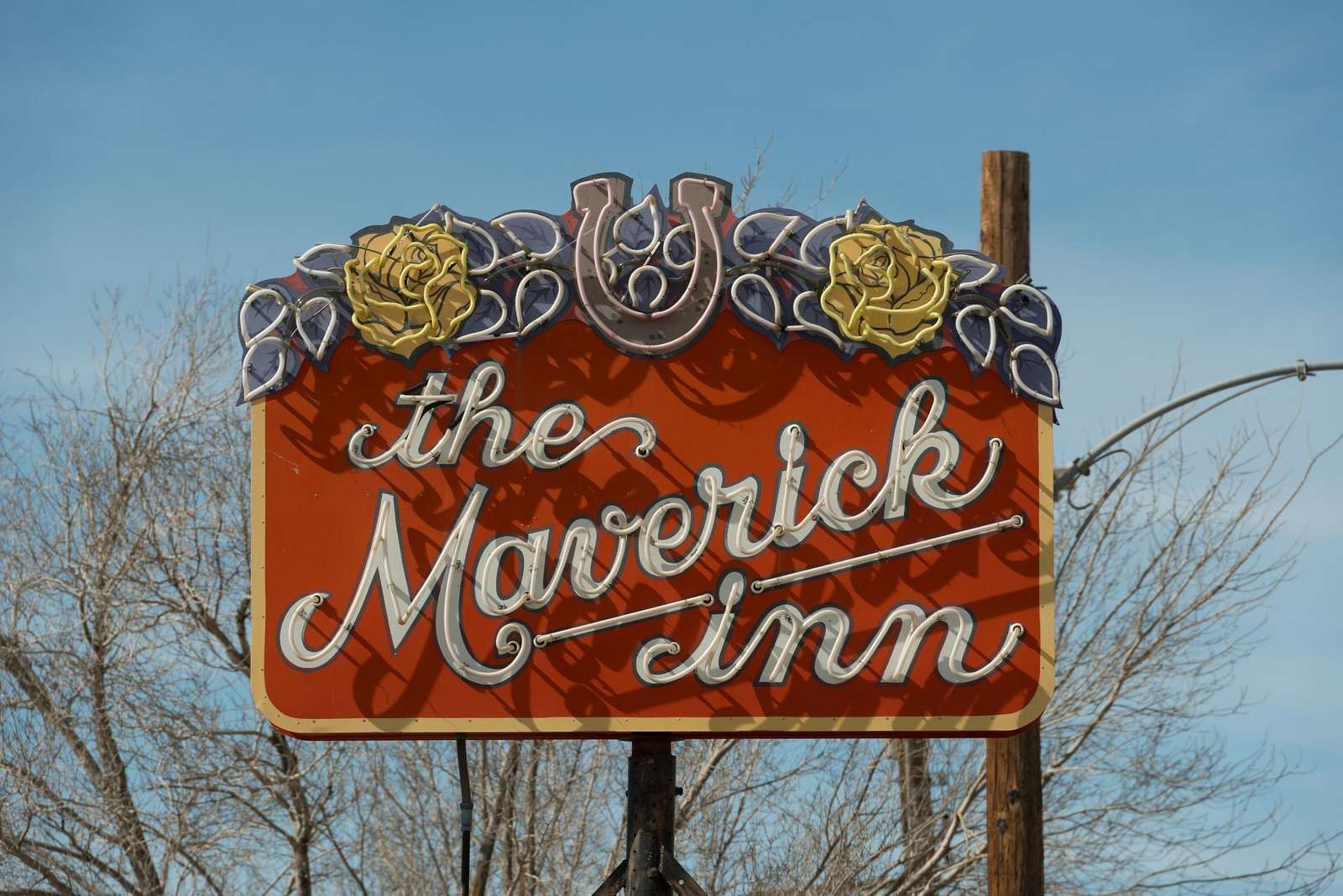 Daytime view of a neon sign for the Maverick Inn in Alpine, Texas