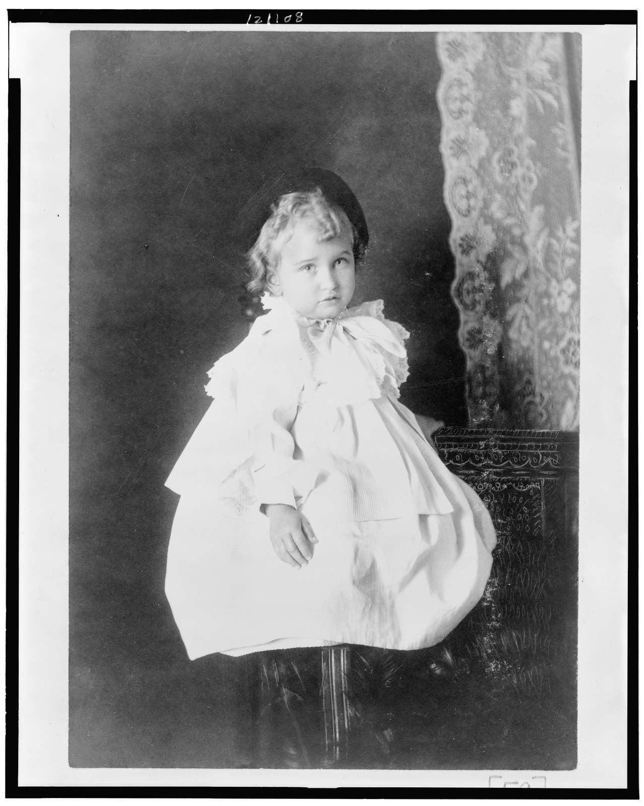 [African American girl, full-length portrait, seated on stool, facing slightly right]