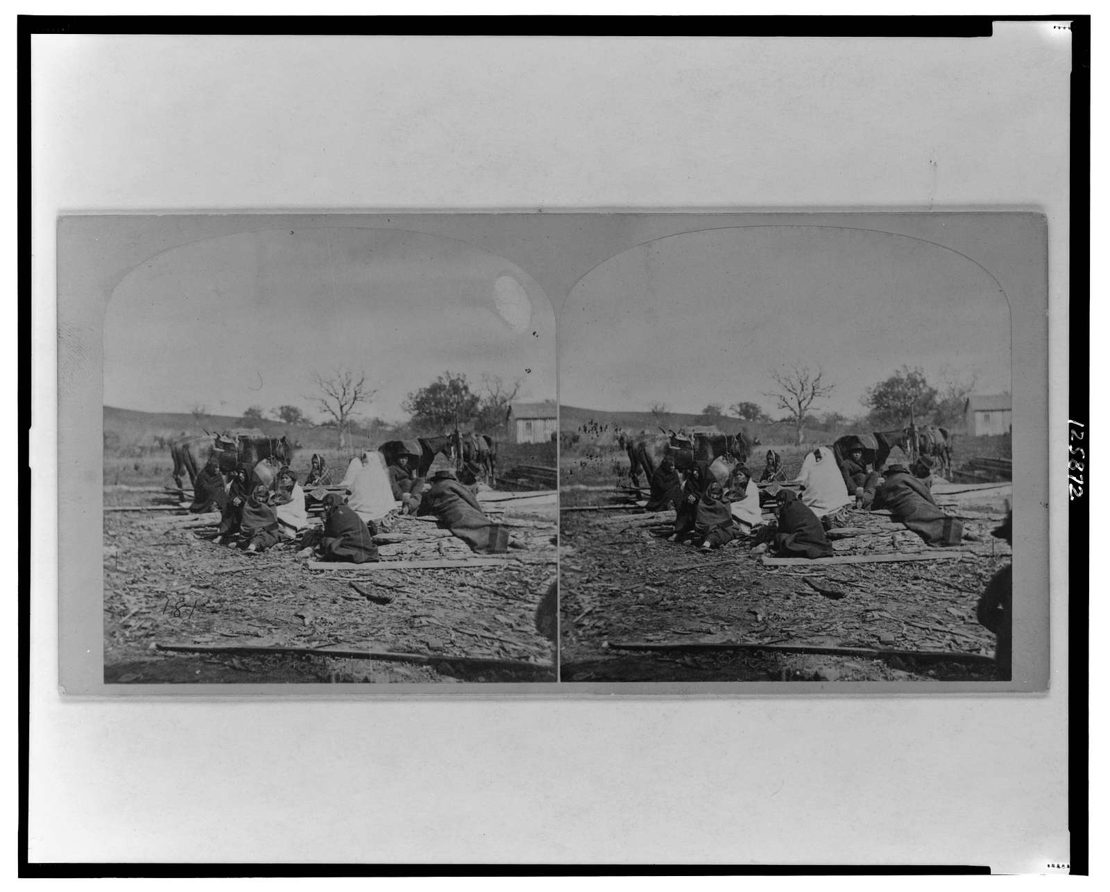 Group of Winnebego Indians seated on ground and logs