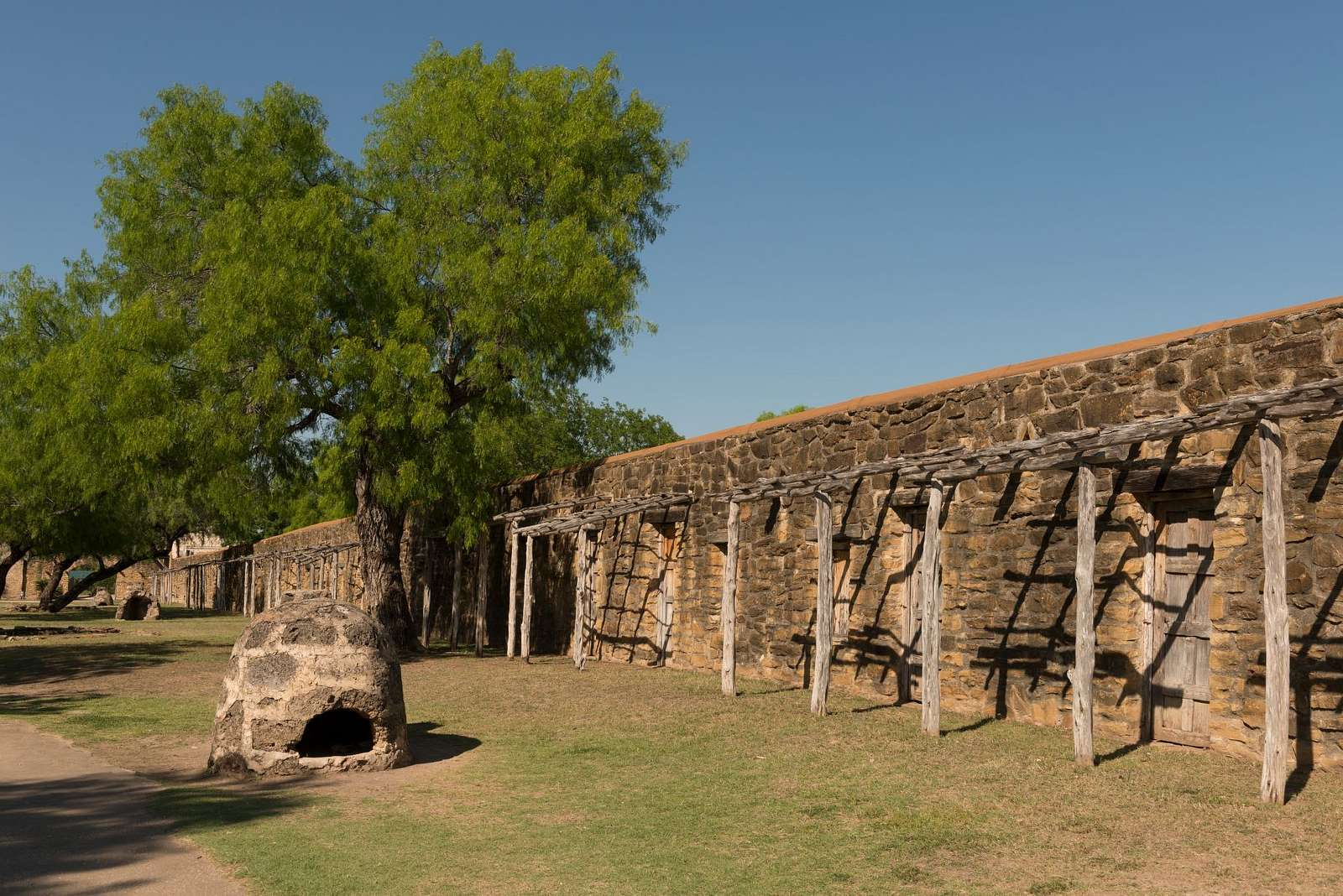 "Stone wall, a brick oven, and a simple arbor at Mission Nuestra Senora de la Purisima Concepcion de Acuna, better known as simply ""Mission Concepcion"" today, is one of four surviving Spanish missions in San Antonio, Texas"