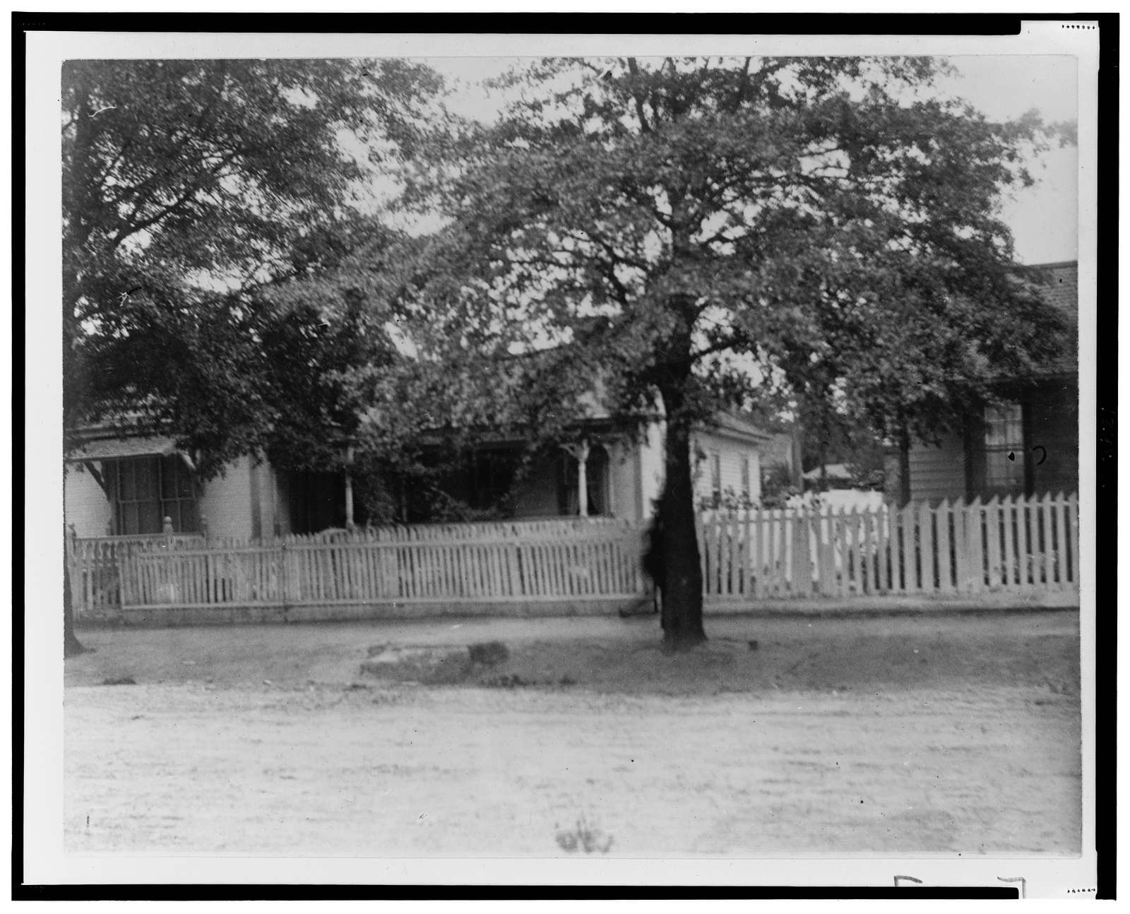 [Houses with picket fence on unpaved road in Georgia]