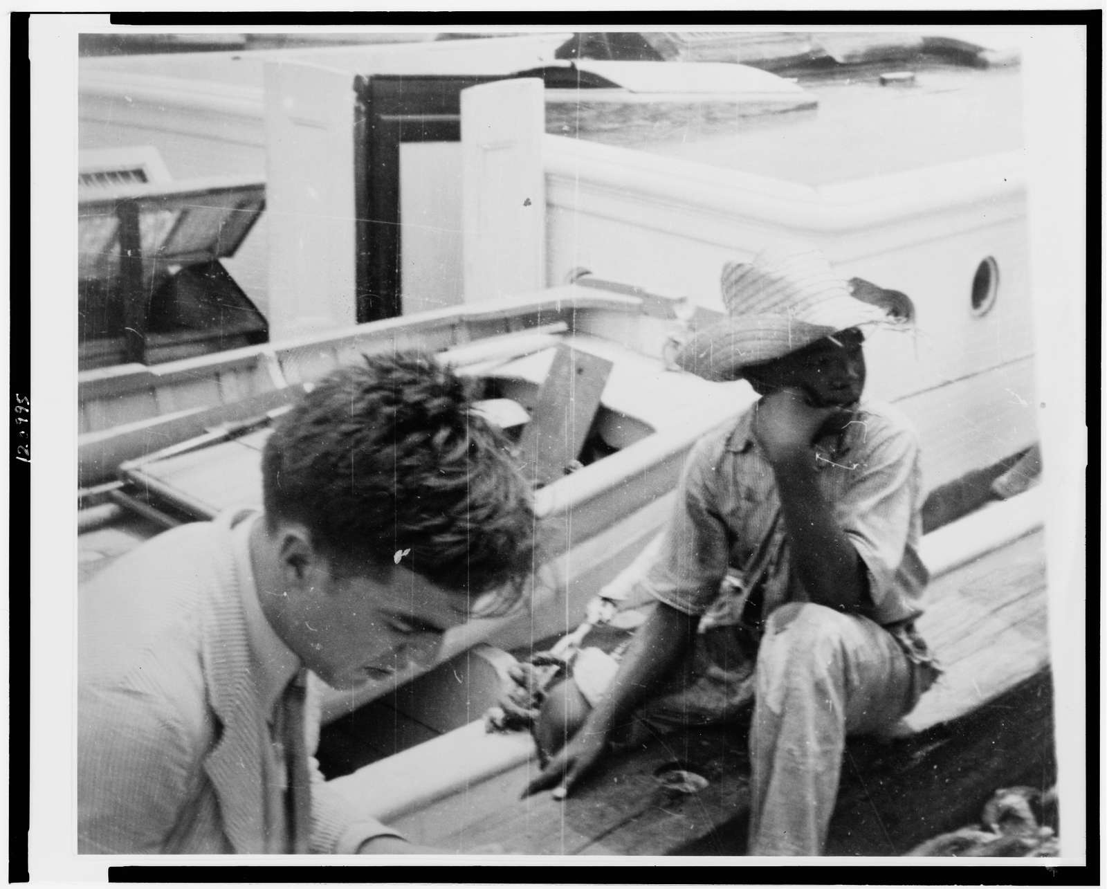 [Alan Lomax (left) youngster on board boat, during Bahamas recording expedition]