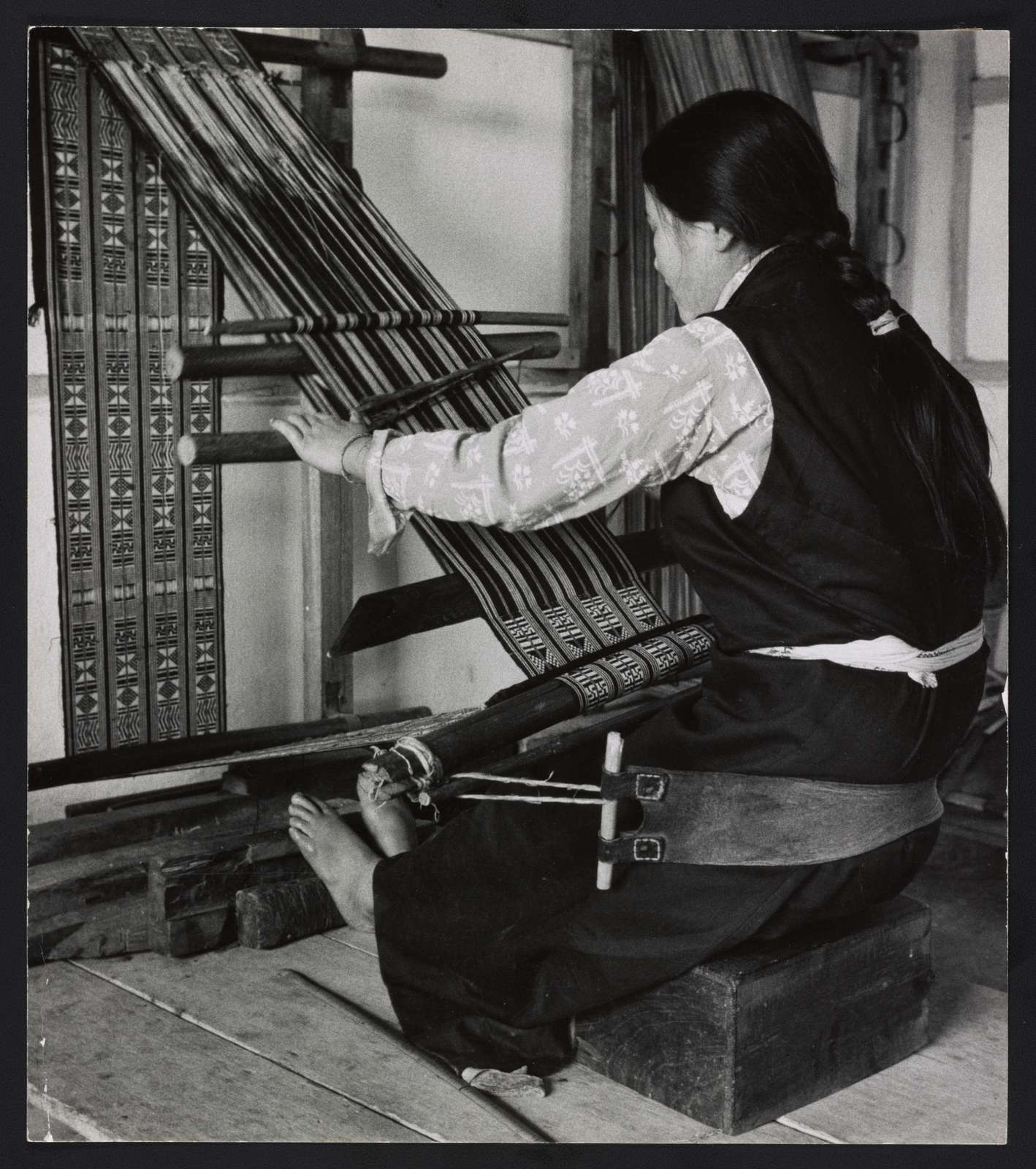 Ancient art of weaving with self-supported back-strap loom. [...] This Sikkimese girl is weaving Lepcha tribal weave cloth worn as a dress