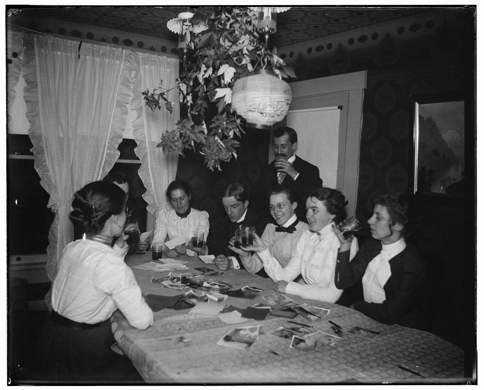 [Orville Wright and group around a table, looking at photographs, during a party at 7 Hawthorn Street]