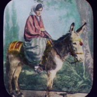 Young woman riding burro