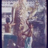 Bangkok - detail of Wat Chang; 2 small boys at foot of warrior figure