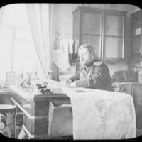 M. Kamorsky - Russian officer at his desk with large map spread - Khabarovsk