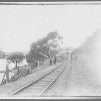 Pedestrian bridge over railroad track beside pond