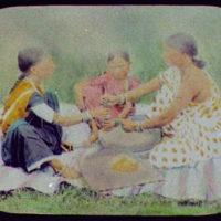 Three women grinding food on flat stones