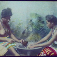 Two bare-breasted women around cooking pot