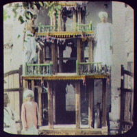 Two men standing on 2nd tier of 3-tiered shrine
