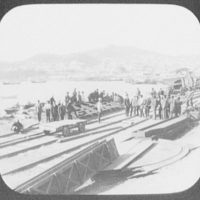 Vladivostok - laborers at dockside railroad tracks; city and harbor in background