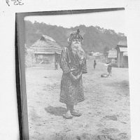 Ainu chief wearing a headdress standing in the village lane