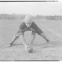 Charlotte Hall Military Academy. Football player, crouched with ball